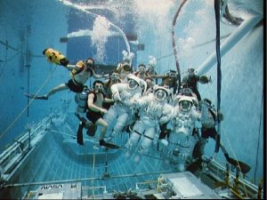 Simulation at JSC's Weightless Environment Training Facility was conducted with extravehicular mobility unit suited astronauts F. Story Musgrave, Michael R. U. Clifford, and James S. Voss. Credit: NASA