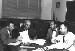Director of the Space Task Group Robert Gilruth (second from left) with, from left to right, chief assistants Charles Donlan, Maxime Faget, and Robert Piland. Here, these original members of the Space Task Group discuss contractors to study feasibility of a manned circumlunar mission. August, 1960. Credit: NASA