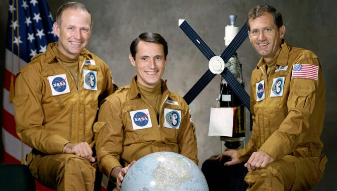 Pictured in their flight suits with a globe and a model of the Skylab space station are, left to right, astronaut Gerald P. Carr, commander; scientist-astronaut Edward G. Gibson, science pilot; and astronaut William R. Pogue, pilot. Credit: NASA