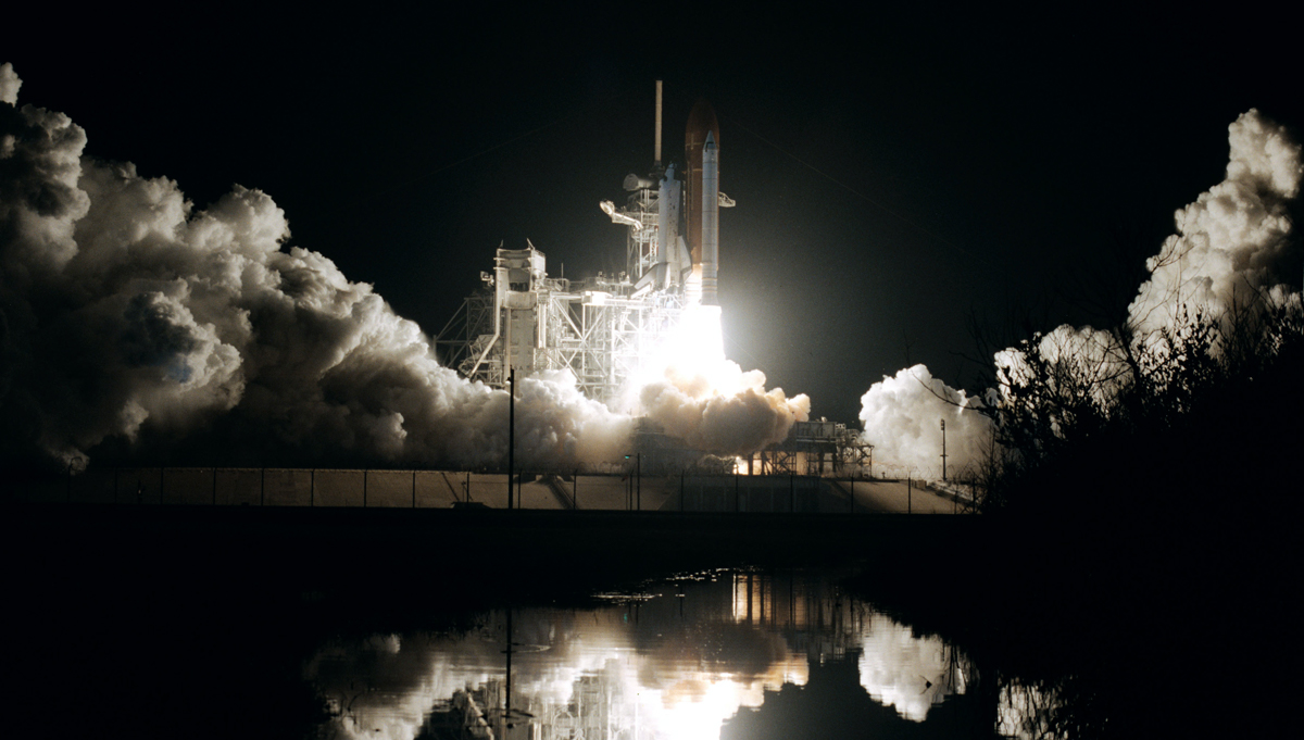 The Space Shuttle Columbia launches before dawn on January 12, 1986 with a tight-knit crew that deployed a key communications satellite. Credit: NASA