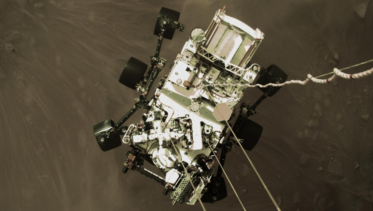 The Perseverance Rover is lowered to the surface of Mars by the Descent Stage, via nylon cables. A camera aboard the descent stage captured this shot. Credit: NASA/JPL-Caltech