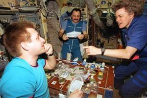 Lucid talks to Usachev (back) and Onufriyenko (front) at the work table in Mir's Base Block. Credit: NASA