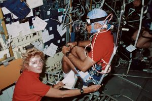 Astronaut James P. Bagian, STS-40 mission specialist, is in a rotating chair while wearing an accelometer and electrodes to record head motion and horizontal and vertical eye movements during the rotations. Payload specialist Millie Hughes-Fulford, lower left, assists with the test. Credit: NASA