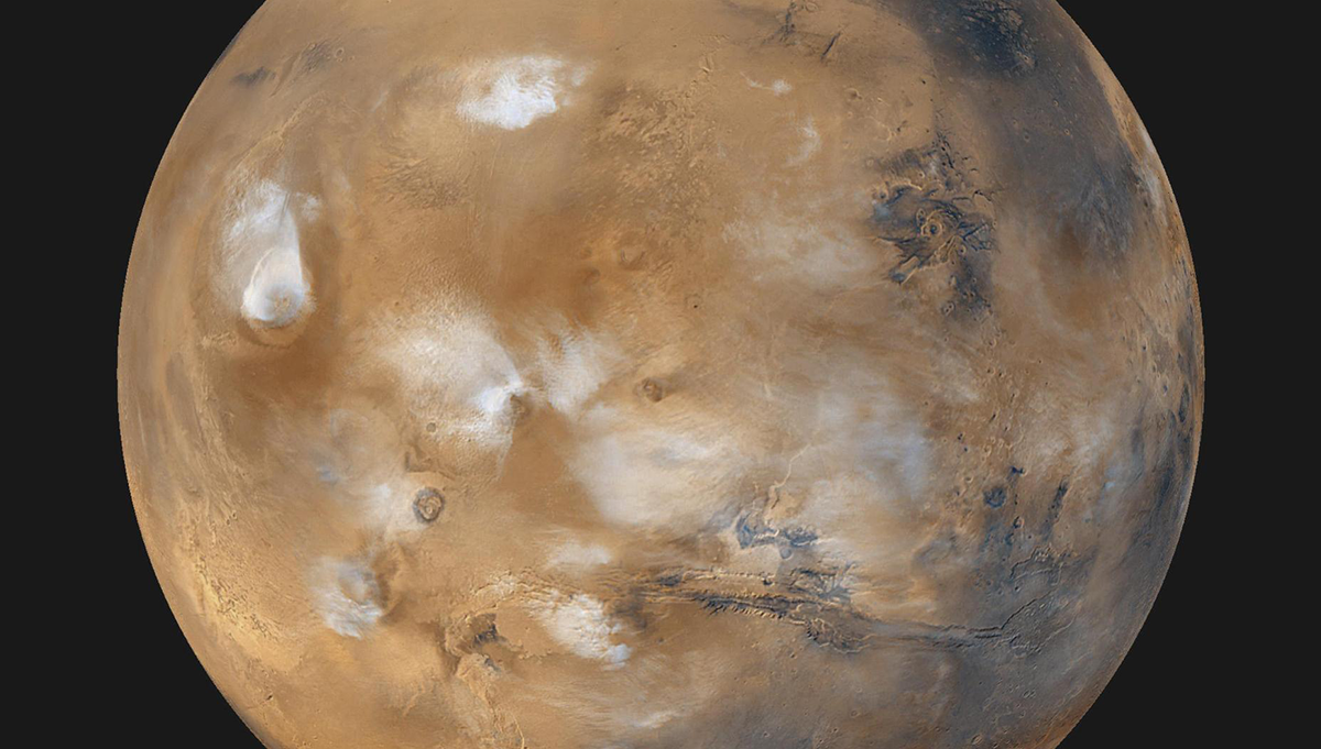 Twelve orbits a day provide the MOC wide angle cameras on NASA's Mars Global Surveyor with a global snapshot of weather patterns across the planet. Here, bluish-white water ice clouds hang above the Tharsis volcanoes. Credit: NASA