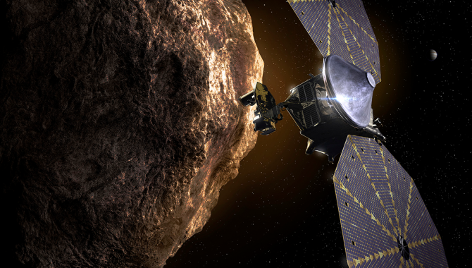 This artist's illustration depicts the Lucy spacecraft passing one of the Jupiter Trojan Asteroids. Lucy will travel 4 billion miles in 12 years, passing by seven of these asteroids, believed to be remnants from the formation of the planets. Credit: Southwest Research Institute